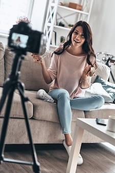 Moderne vloggers. mooie jonge vrouw die schoonheidsproducten vasthoudt en glimlacht terwijl ze video op sociale media maakt