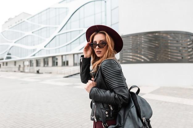 Moderne vrij stijlvolle hipster jonge vrouw in een modieuze hoed in vintage donkere zonnebril in een zwarte jas met een leren rugzak