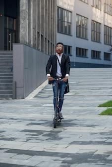 Moderne vrolijke zwarte zakenman rijdt elektrische scooter na het beëindigen van zijn werkdag op kantoor.