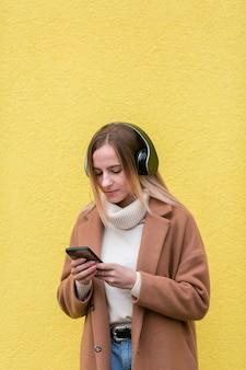 Moderne vrouw die aan muziek op hoofdtelefoons luistert