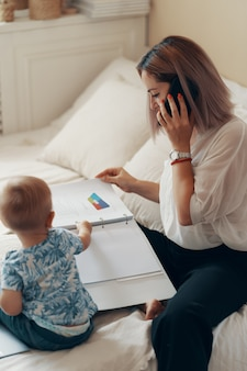 Moderne vrouw die met kind werkt. multi-tasking, freelance en moederschap concept