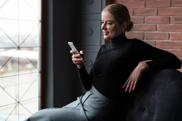 Moderne vrouw die mobiel bekijkt