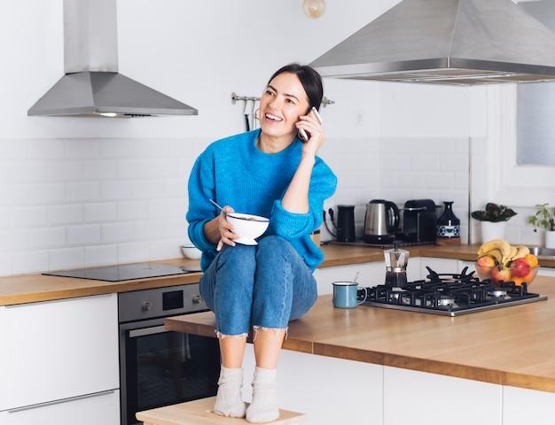 Moderne vrouw die ontbijt in de keuken heeft