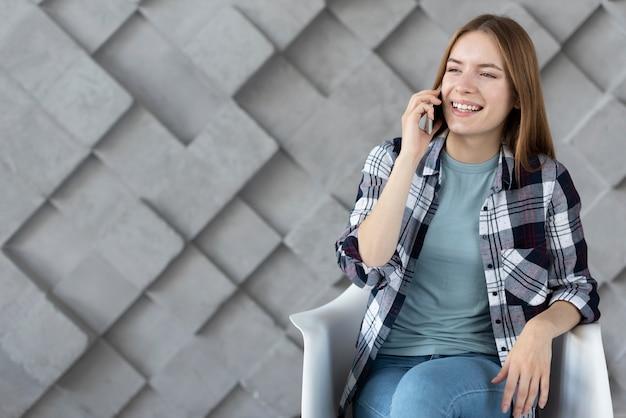 Moderne vrouw die op telefoon met exemplaarruimte spreekt