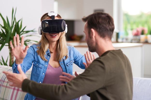 Moderne vrouw die virtual reality-simulator in de woonkamer gebruikt