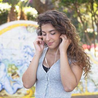 Moderne vrouw het luisteren muziek in het park