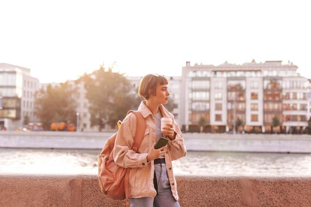 Moderne vrouw in denim outfit met bruine rugzak met kopje koffie in de stad