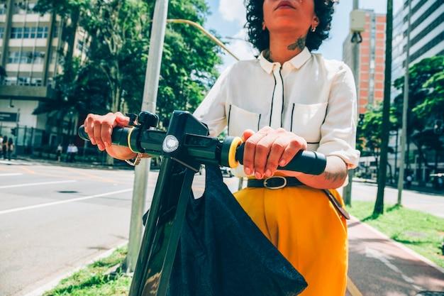 Moderne vrouw in een stad met een elektrische autoped