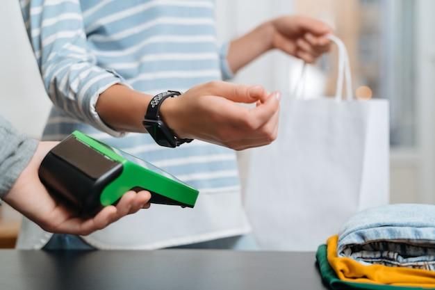 Moderne vrouw met behulp van terminal voor contactloze betaling met smartwatch op balie in kledingwinkel
