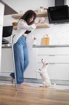Moderne vrouwelijke huisdiereneigenaar die het voeden van opleidingshond speelt bij het jack russell terrier-ras in de keuken
