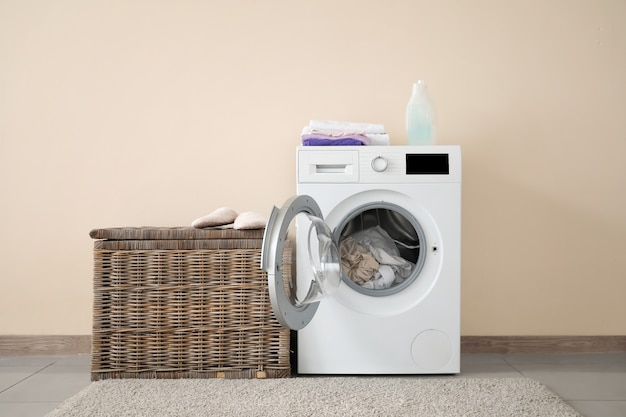 Moderne wasmachine met wasgoed in de buurt van kleurenmuur