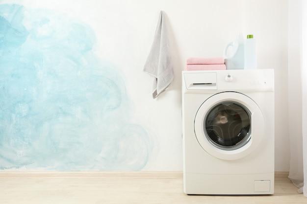 Moderne wasmachine tegen blauwe muur, ruimte voor tekst