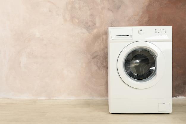 Moderne wasmachine tegen bruine muur, ruimte voor tekst