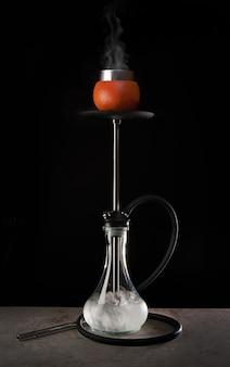 Moderne waterpijp met glazen kom en grapefruitaroma op zwarte achtergrond