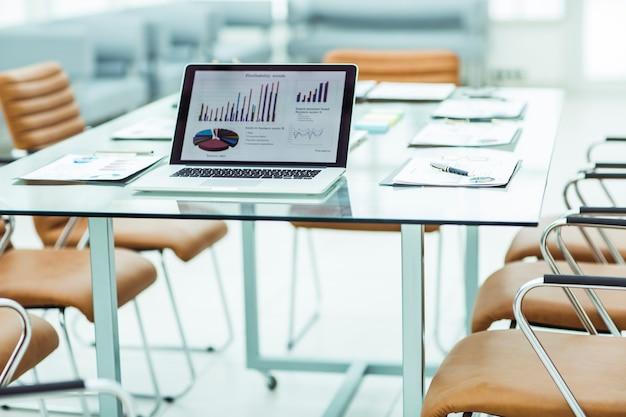 Moderne werkplek met opengeklapte laptop en financiële documenten die zijn voorbereid om zakenpartners te ontmoeten. de foto is een lege ruimte voor uw tekst