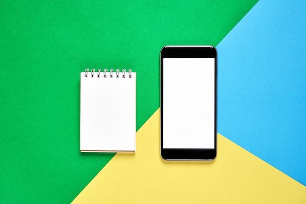 Moderne werkplek met smart phone en pagina's zijn leeg