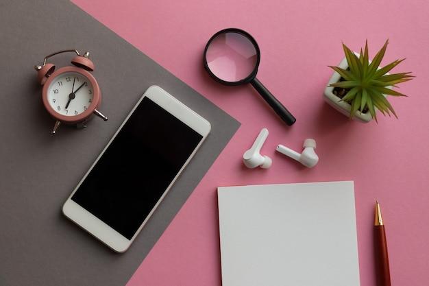 Moderne werkplek met smartphone notitieblok pen wekker plant vergrootglas en koptelefoon op roze en grijze geometrische tafel
