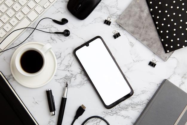 Moderne werkplekregeling op marmer met lege telefoon