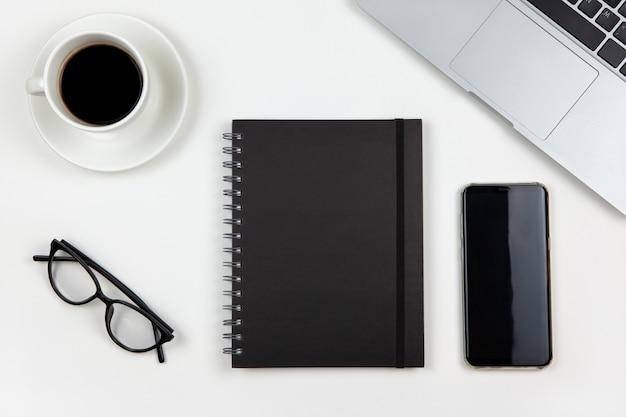 Moderne werkruimte, bovenaanzicht. laptop, koffie, blocnote, smartphone, bril