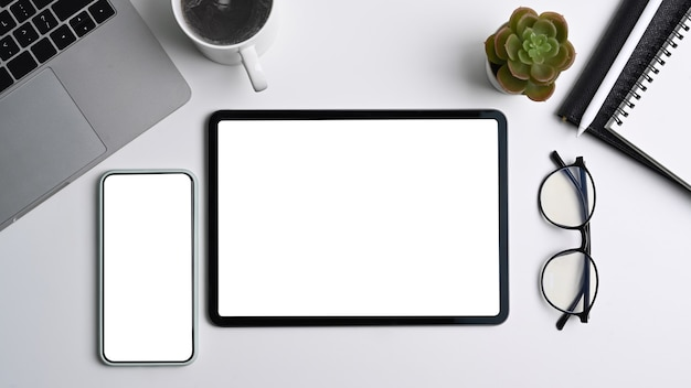 Moderne werkruimte met digitale tablet, smartphone, laptopcomputer en bril op witte tafel.