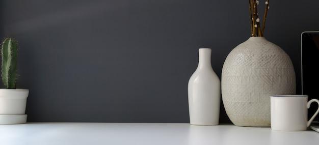 Moderne werkruimte met kopie ruimte en keramische vaas op witte tafel en grijze muur