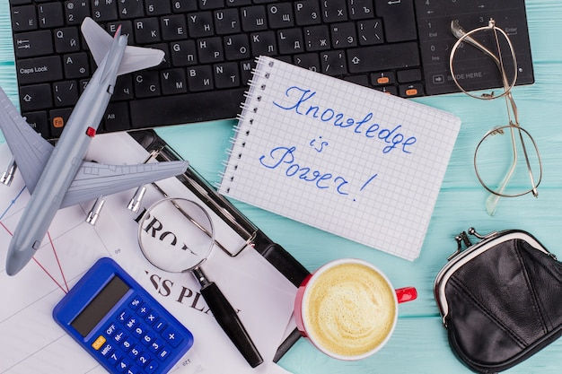 Moderne werkruimte met toetsenbord, koffiekopje kladblok brillen op blauwe achtergrond. kennis is macht op notebook. platliggende stijl.