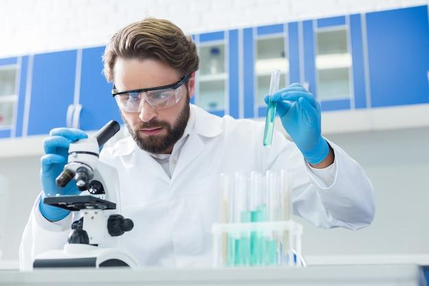 Moderne wetenschap. ernstige intelligente aangename man zit aan de tafel en houdt een reageerbuis vast terwijl hij in het laboratorium werkt