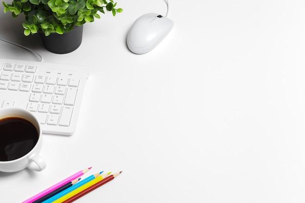 Moderne witte bureautafel met computertoetsenbord en benodigdheden.