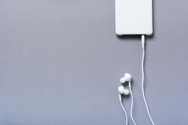 Moderne witte oortelefoons en mobiele telefoon op een grijze achtergrond. minimalistische stijl. bovenaanzicht met kopie ruimte.