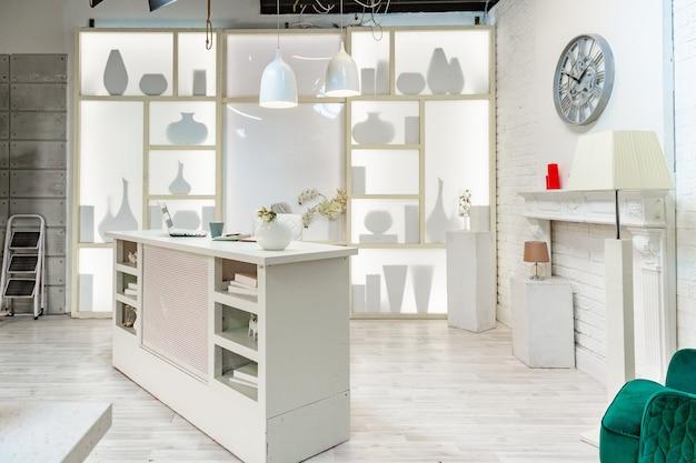 Moderne witte studio. met een lichtstandaard in het midden, met een speciale lamp op de achterwand.