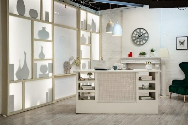 Moderne witte studio. met een lichtstatief in het midden, met een speciaal licht op de achterwand.