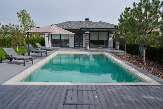 Moderne woning met zwembad. grondgebied met ligstoelen en houten vloer. volledige lengte weergave. modern villaconcept