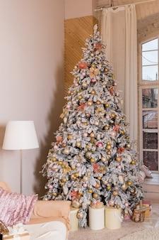 Moderne woonkamer, comfortabele bank en kerstboom en cadeautjes eronder in grote suite.