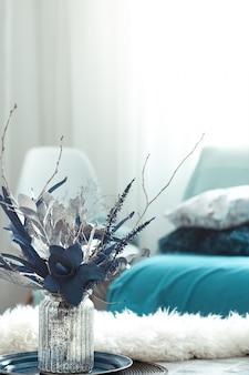 Moderne woonkamer, met kunstbloemen in een vaas en home decor items op houten licht tafel.