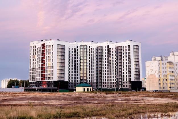 Moderne woonwijk bij zonsondergang laat in de avond. late herfst. modder en plassen aan de rand van de stad. woongebouwen met meerdere verdiepingen. hypotheek voor jonge gezinnen.
