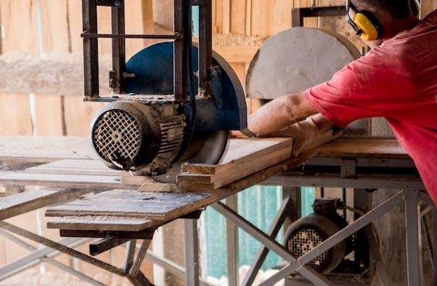 Moderne zagerij. een timmerman werkt aan houtbewerking van de werktuigmachine.
