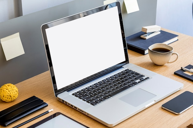Moderne zakelijke compositie op het houten bureau met laptopscherm, tablet, notities, mobiele telefoon, kopje koffie en kantoorbenodigdheden in stijlvol concept van huisdecor.