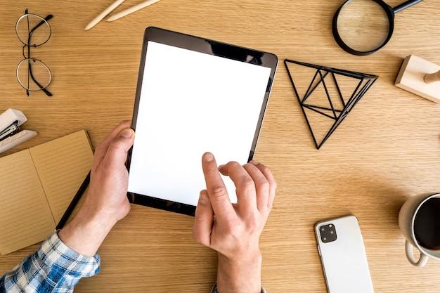 Moderne zakelijke compositie op het thuiskantoor met freelancer, mock-up tabletscherm, plant, notities, mobiele telefoon en kantoorbenodigdheden in stijlvol concept van huisdecor.