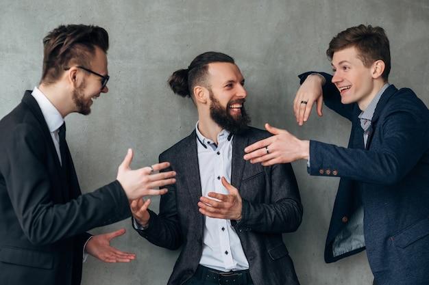 Moderne zakelijke leven. positieve kantoorsfeer. mannelijke collega's praten, lachen, plezier maken tijdens de pauze op het werk.