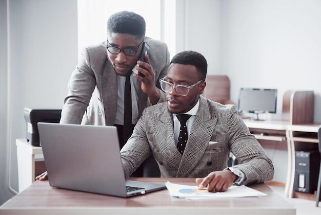 Moderne zakenman aan het werk. twee vertrouwen in mensen uit het bedrijfsleven in formalwear bespreken iets en kijken naar de laptop-monitor