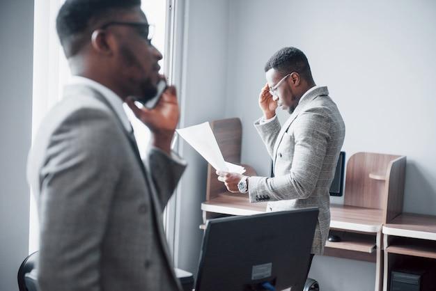 Moderne zakenman aan het werk. twee zelfverzekerde zakenmensen in formalwear bespreken iets terwijl een van hen de documenten bekijkt en de tweede een belangrijk telefoontje