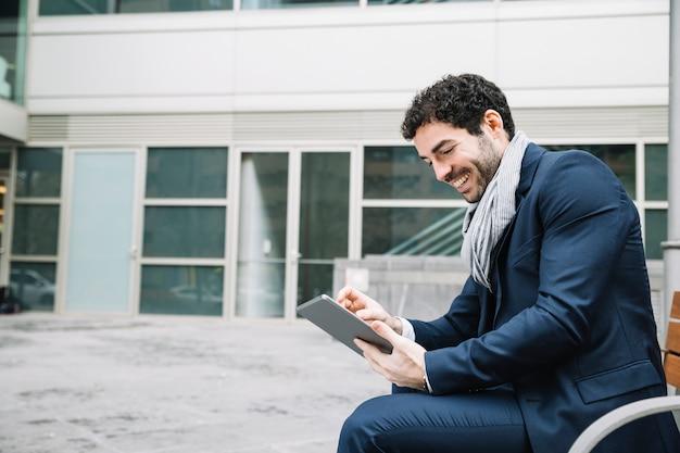 Moderne zakenman die apparaat in openlucht met behulp van