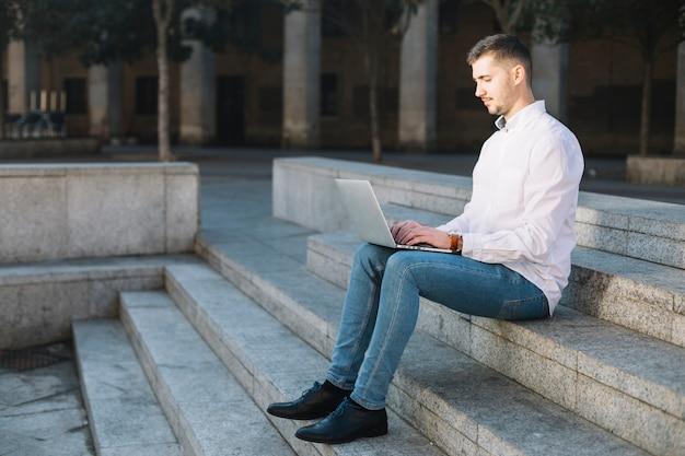 Moderne zakenman die laptop in openlucht met behulp van
