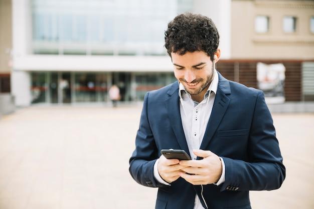 Moderne zakenman die smartphone in openlucht gebruikt
