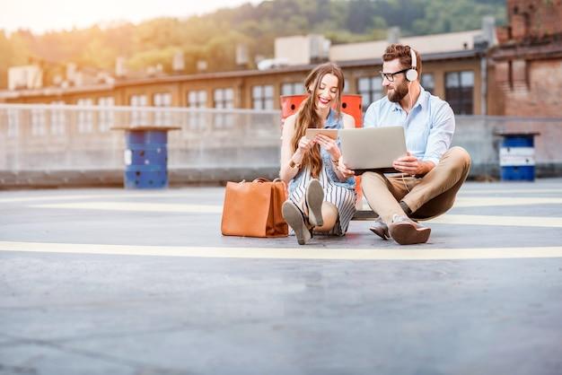 Moderne zakenman en zakenvrouw werken met laptop en telefoon zittend op de helihaven grond. lifestyle bedrijfsconcept