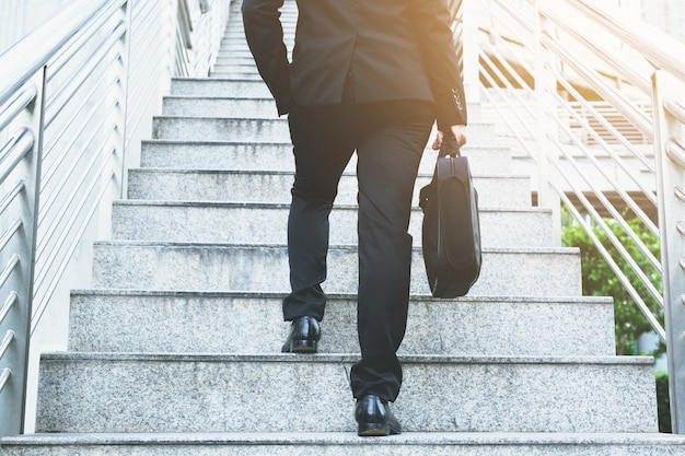Moderne zakenman hand met aktetas naast werken close-up benen lopen de trap op in de moderne stad. in de spits naar het werk op kantoor haast.