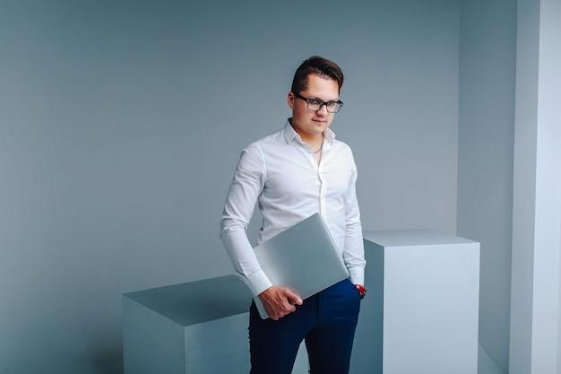 Moderne zakenman in een wit shirt, blauwe broek en bril met een laptop in de studio