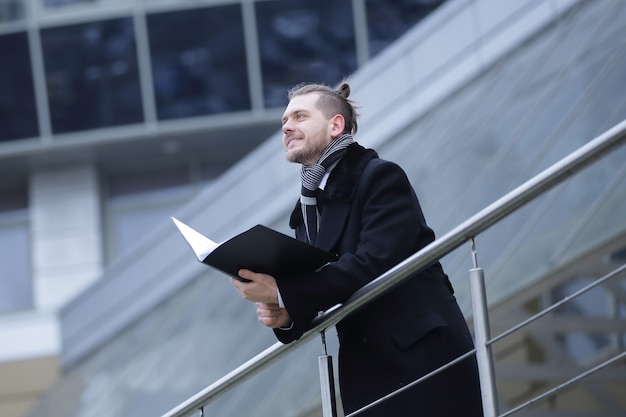 Moderne zakenman met papieren, komt zijn kantoor binnen