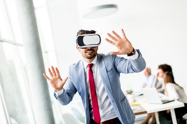 Moderne zakenman met virtuele werkelijkheidshoofdtelefoon in het bureau