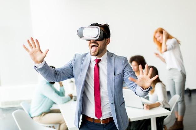 Moderne zakenman met virtuele werkelijkheidshoofdtelefoons in het bureau